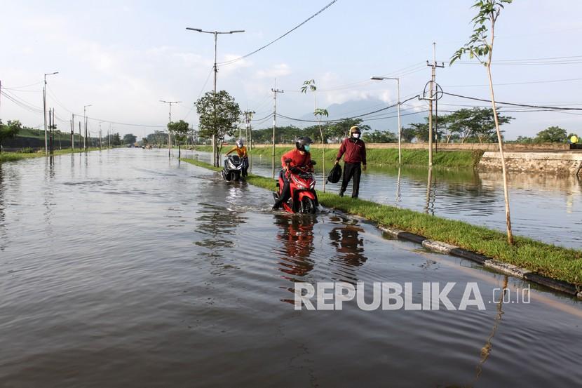 Pengendara mendorong sepeda motor menerobos banjir yang menggenangi jalan raya Porong, Sidoarjo, Jawa Timur, Selasa (16/2/2021). Curah hujan yang tinggi sejak Senin (15/2) malam mengakibatkan banjir yang merendam jalan raya Porong sehingga mengganggu kelancaran transportasi umum.