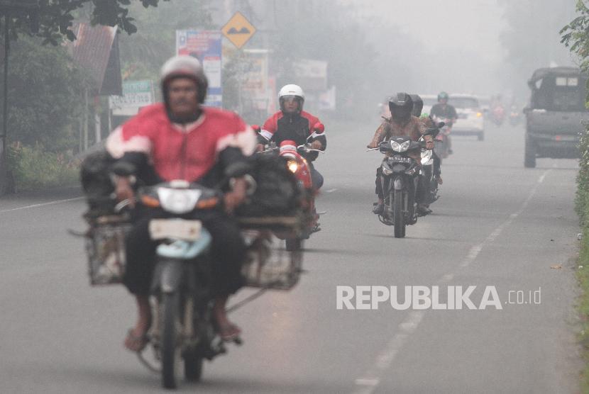 Pengendara menembus kabut asap yang menutupi jalanan.