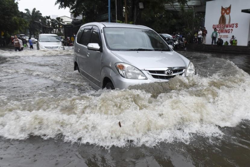 Pengendara mobil berusaha menerobos banjir