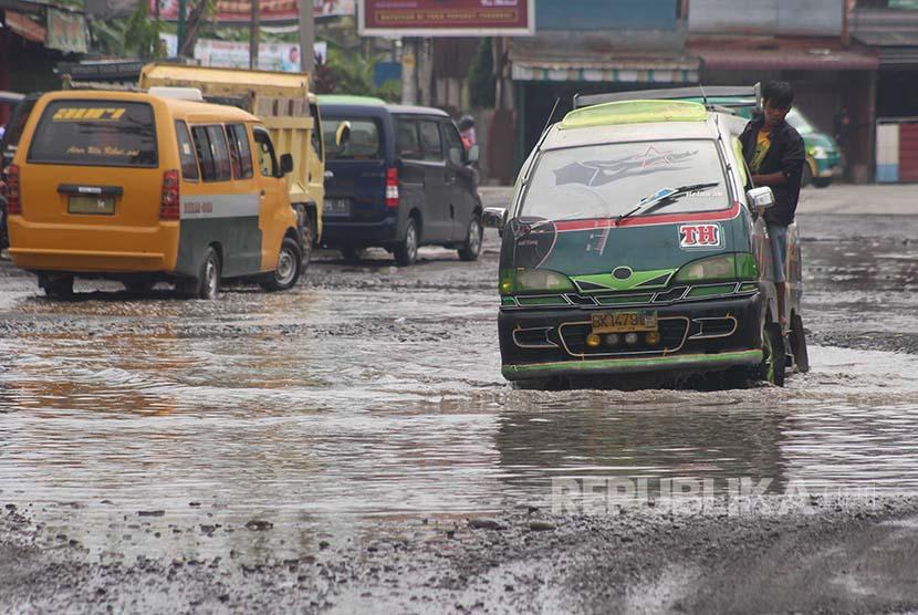 [ilustrasi] Pengendara mobil berusaha menghindari jalan rusak yang terendam air di kawasan Jalan Titi Papan Medan, Sumatra Utara.engganggu aktivitas masyarakat. Kondisi jalan rusak di Medan juga dinilai sebagai salah satu penyebab banyaknya kasus pembegalan.