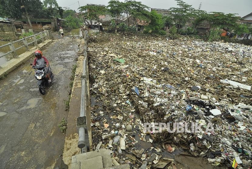 Pengendara motor melintas di samping tumpukan sampah (ilustrasi)