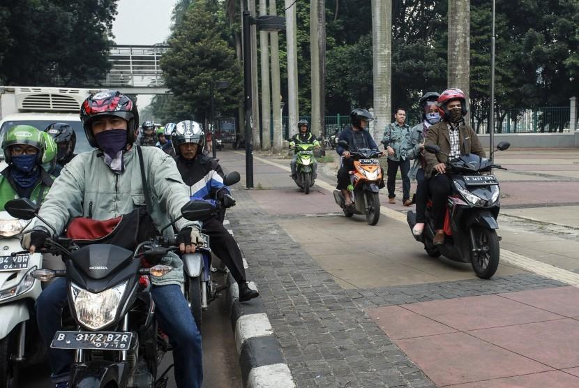 Pengendara motor mengendarai motornya diatas jalur pejalan kaki (trotoar) di kawasan jalan Jenderal Sudirman, Jakarta, Selasa (17/5).