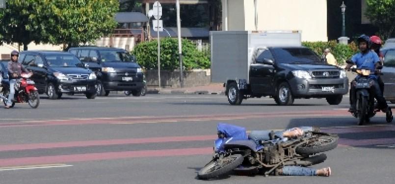 Pengendara motor terjatuh saat bersinggungan dengan kendaraan lain di persimpangan Sarinah, Jakarta Pusat, Selas (21/2).