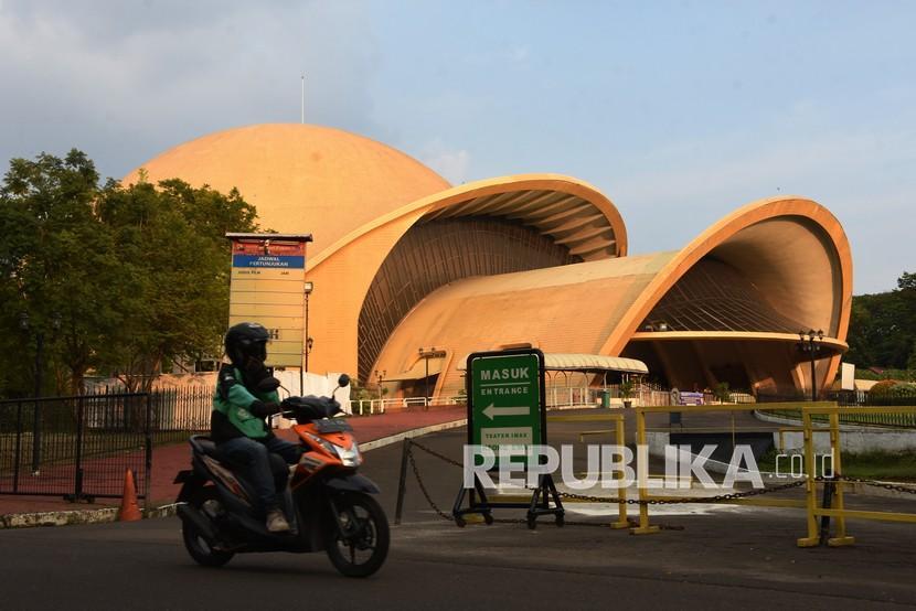Pengendara ojek daring melintas di depan anjungan Keong Emas, Taman Mini Indonesia Indah, Jakarta.