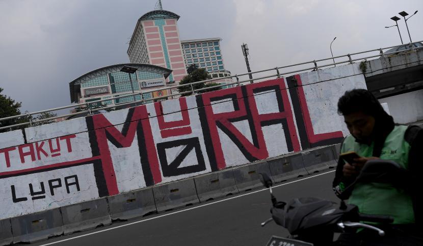 Pengendara ojek daring menunggu penumpang di depan mural yang berisi kritikan di Jakarta Barat, Ahad (19/9/2021). Presiden Joko Widodo meminta aparat kepolisian tidak berlebihan dalam menanggapi kritik masyarakat terhadap pemerintah yang disampaikan melalui mural.