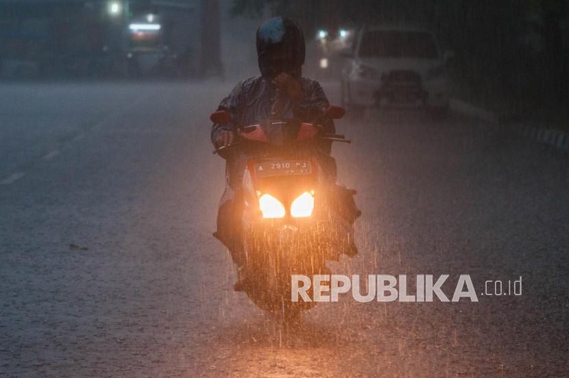Pengendara roda dua menerobos hujan di. BMKG mengeluarkan peringatan dini prakiraan hujan lebat disertai kilat dan angin kencang yang berpotensi terjadi di beberapa wilayah Indonesia. (ilustrasi)
