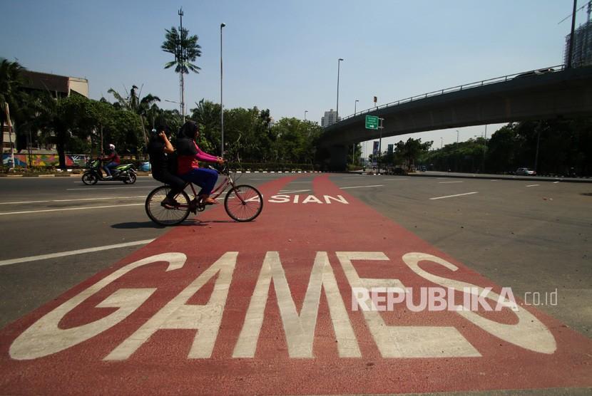 Pengendara sepeda melintasi jalur prioritas kendaraan untuk Asian Games 2018 di Kemayoran, Jakarta, Jumat (27/7).