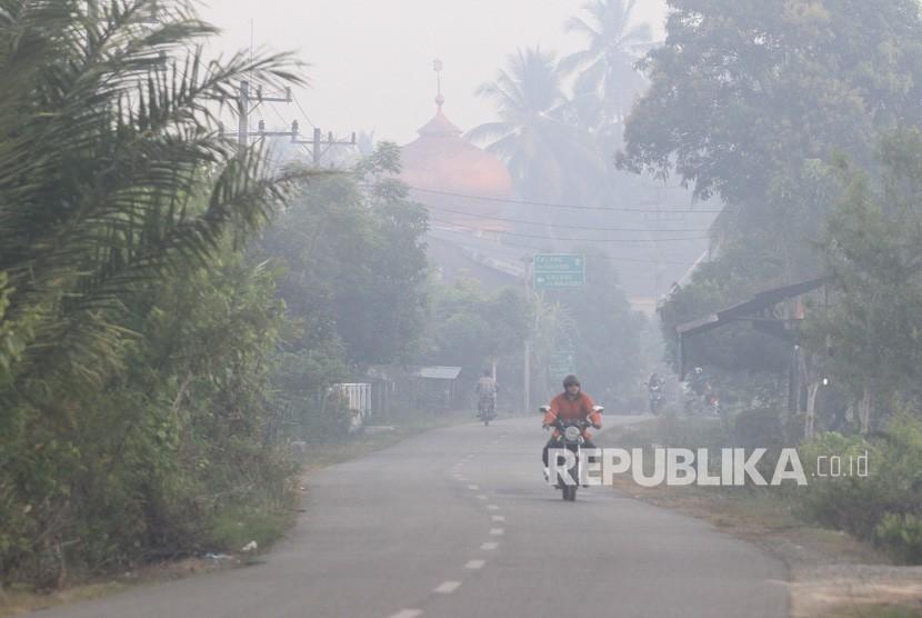 Pengendara sepeda motor melaju menembus kabut asap akibat Kebakaran Hutan dan Lahan (Karhutla) saat melintasi jalan Desa Pinem, Kecamatan Samatiga, Aceh Barat, Aceh, Selasa (6/8/2019).