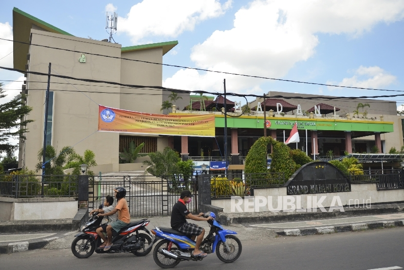 Pengendara sepeda motor melintas dekat Hotel Grand Madani di Mataram, NTB, Ahad (4/6).