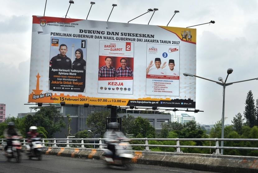 Pengendara sepeda motor melintas di dekat baliho sosialisasi Pilkada Gubernur dan Wakil Gubernur DKI Jakarta Tahun 2017 di Jakarta, Jumat (10/2).