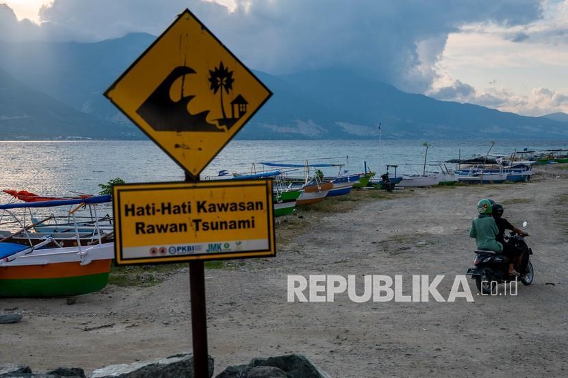 Pengendara sepeda motor melintas di dekat tambatan perahu di Pantai Teluk Palu, Sulawesi Tengah, Senin (26/4/2021). Pemerintah dan sejumlah Lembaga Swadaya Masyarakat (LSM) melakukan mitigasi bencana dengan memasang papan peringatan kawasan rawan tsunami di sejumlah titik di pantai yang telah diterjang lima kali tsunami sejak tahun 1908 itu.