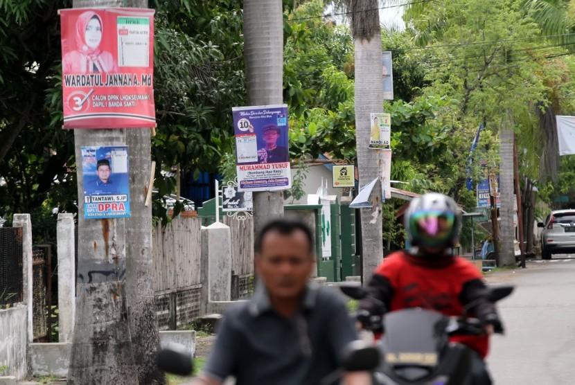Pengendara sepeda motor melintas di jalan yang masih terdapat Alat Peraga Kampanye (ilustrasi)