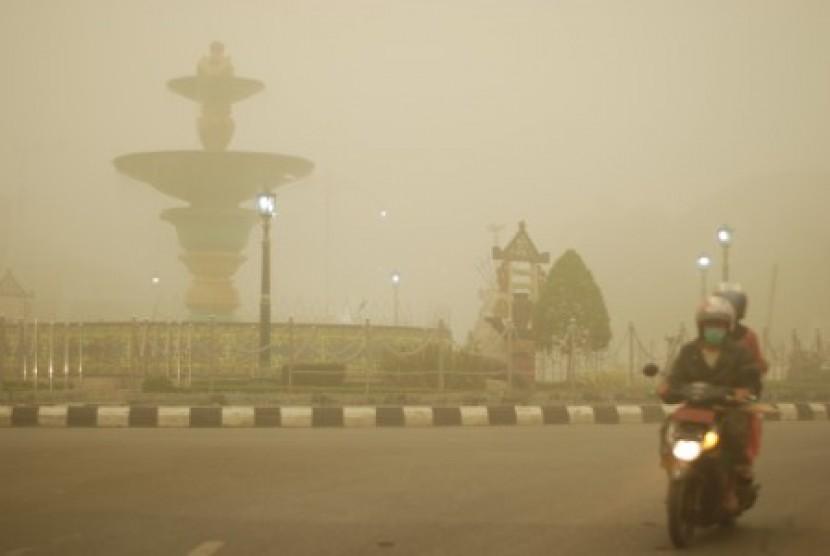 Pengendara sepeda motor melintas di kawasan Bundaran Air Mancur yang tertutup kabut asap tebal di Muara Teweh, Kabupaten Barito Utara, Kalimantan Tengah, Kamis (22/10).