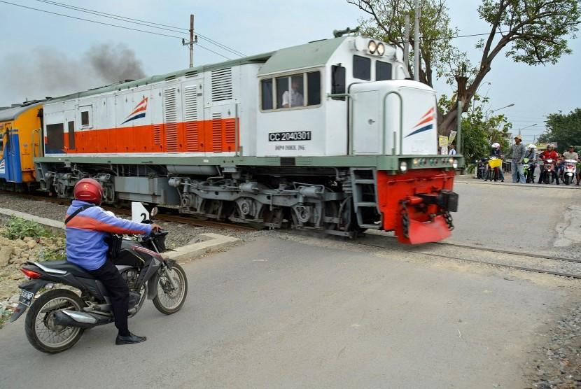 Pengendara sepeda motor menghentikan kendaraannya saat sebuah kereta api melintas di perlintasan kereta api tanpa palang pintu di Kelurahan Kemijen Semarang, Jawa Tengah.