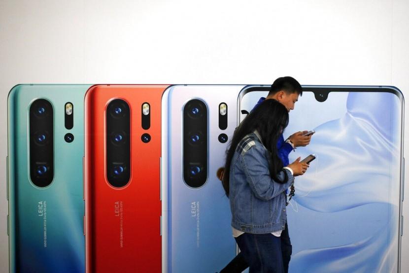Pengguna ponsel melewati iklan Huawei p30 di Beijing, China.