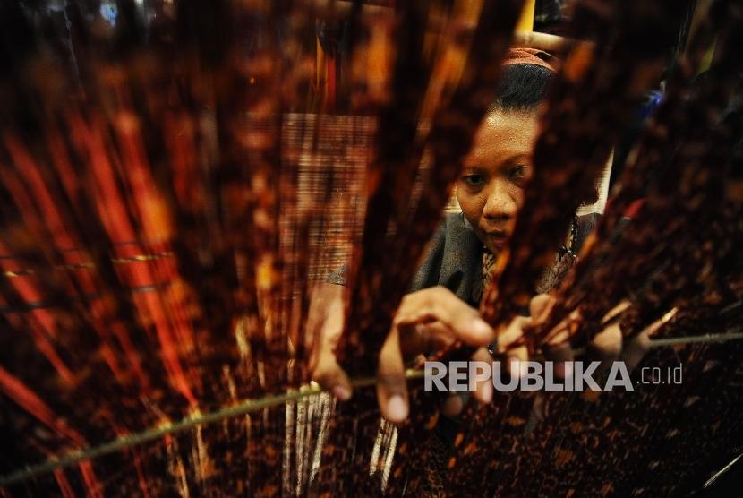 Pengrajin menyelesaikan pembuatan tenun ikat khas Flores pada pameran Inacraft 2016 di JCC, Jakarta. (Republika/Tahta Aidilla)