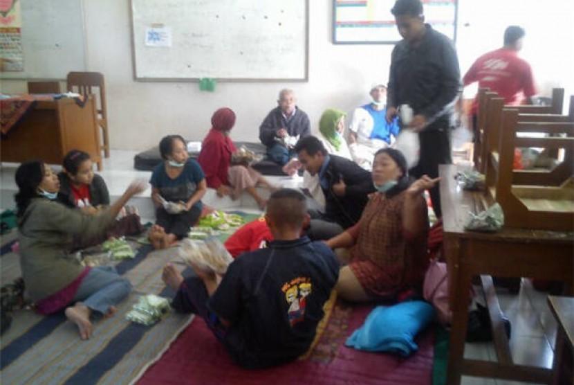 Pengungsi erupsi Gunung Kelud di Kediri, Jawa Timur, menikmati nasi bungkus yang didistribusikan Lembaga Kemanusiaan Nasional PKPU pada Sabtu (15/2).