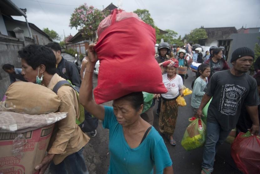 Pengungsi Gunung Agung asal Desa Muncan membawa barangnya saat mereka diantarkan ke kampungnya dari tempat penampungan sementara di Klungkung, Bali, Sabtu (7/10).