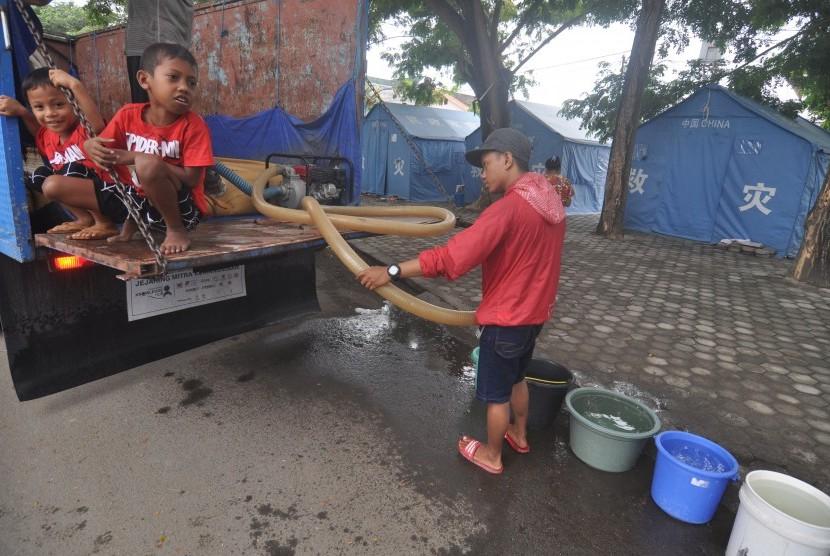 Pengungsi korban bencana gempa, tsunami dan likuifaksi mengambil air bersih yang disalurkan ke tenda hunian mereka di Kamp Pengungsian, Palu, Sulawesi Tengah, Kamis (17/1/2019).