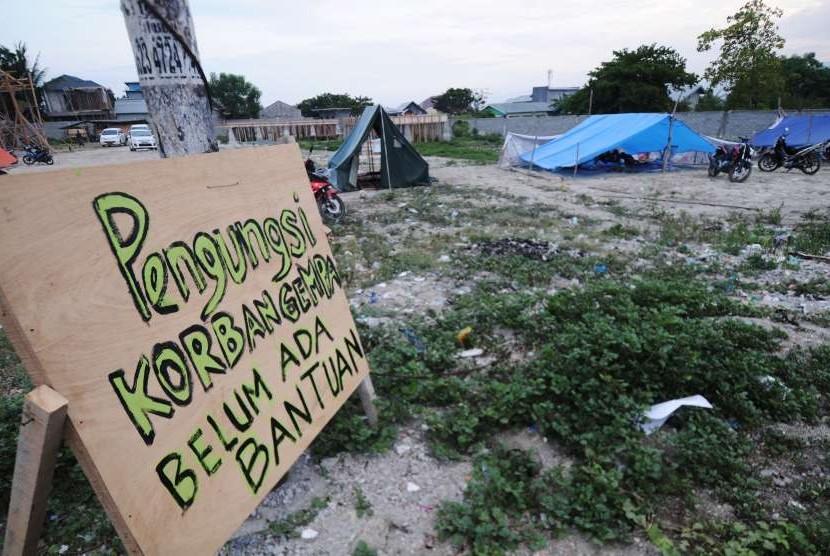 Pengungsi memasang tanda belum mendapat bantuan di salah satu titik pengungsian di Kelurahan Palupi Palu, Sulawesi Tengah, Kamis (4/10).