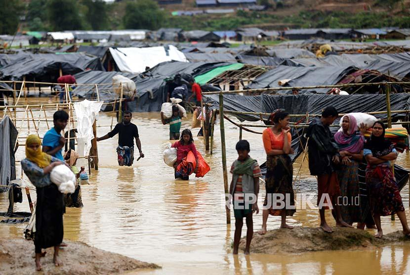 Pengungsi meninggalkan kamp pengungsi Rohingya yang terendam banjir di Cox