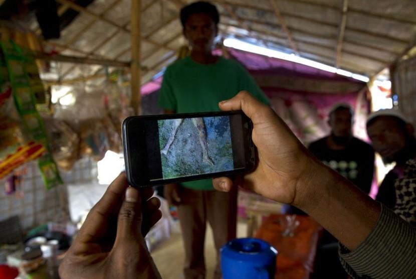 Pengungsi Muslim Rohingya Mohammad Karim menunjukkan video ponsel pembunuhan massal di Gu Dar Pyin di kamp pengungsi Kutupalong, Bangladesh.