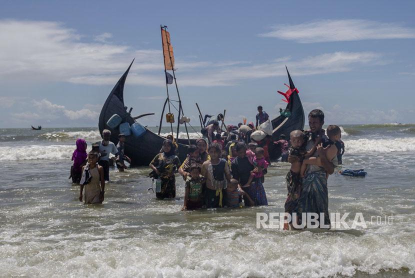 Pengungsi Rohingya berjalan menuju daratan perairan setelah mereka tiba dari Myanmar ke Bangladesh di Shah Porir Dwip, Bangladesh Kamis, (14/9).