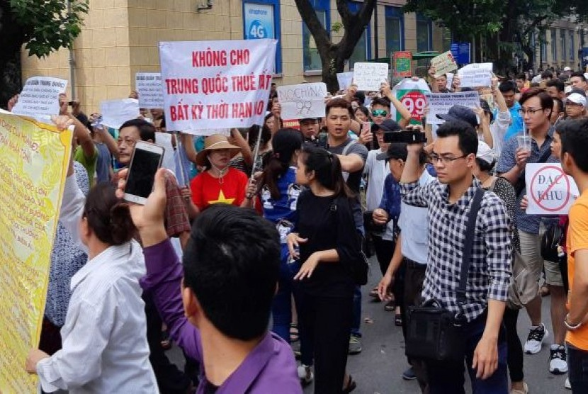 Pengunjuk rasa di Vietnam memegang poster bertuliskan