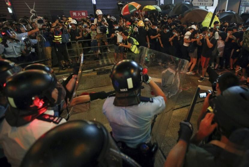 Pengunjuk rasa Hong Kong bergerak mundur saat ditekan polisi dalam protes menentang RUU ekstradisi di Hong Kong, Ahad (77).