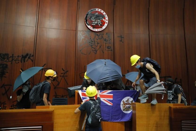 Pengunjuk rasa Hong Kong memasang bendera kolonial dan merusak logo Hong Kong di ruang utama gedung legislatif di Hong Kong, Senin (1/7).