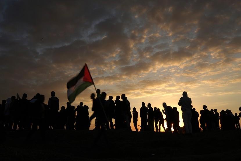 Pengunjuk rasa melambaikan bendera Palestina.