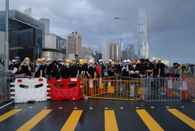 Pengunjuk rasa mengenakan masker ketika mereka berusaha memblokir jalan menuju lokasi peringatan kembalinya Hong Kong ke China di Hong Kong, Senin (1/7).