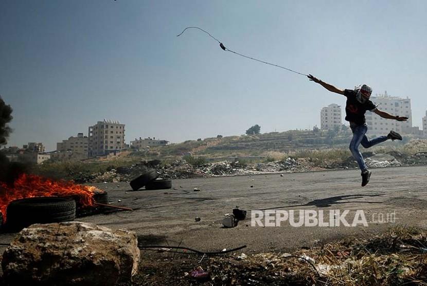 Pengunjuk rasa menggunakan ketapel untuk melemparkan batu di Kota Ramallah, Palestina. Protes dilakukan sebagai dukungan kepada aksi mogok makan yang dilakukan aktivis Palestina yang ditahan oleh Israel.