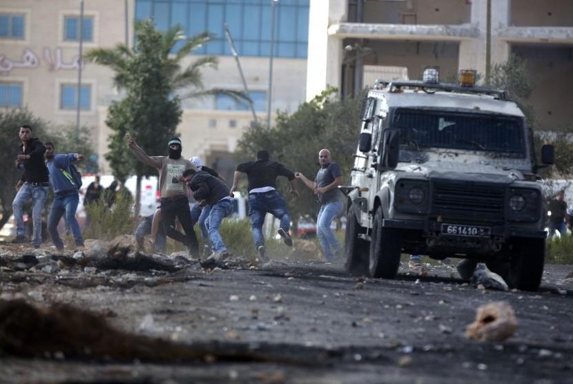 Pengunjuk rasa Palestina melemparkan batu ke kendaraan militer Israel selama bentrokan dengan pasukan Israel di dekat Ramallah, Tepi Barat, Kamis, 8 Oktober 2015.