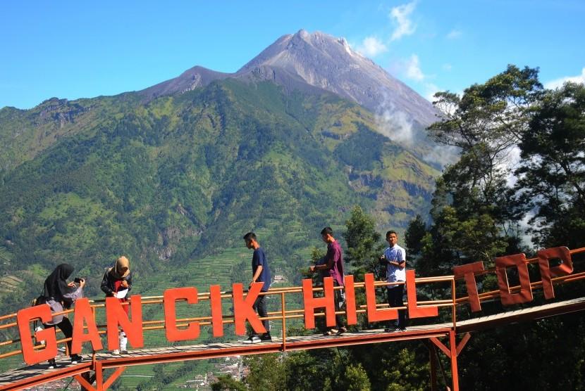 Pengunjung berada di jembatan gardu pandang wisata Gancik di lereng Gunung Merbabu, Selo, Boyolali, Jawa Tengah, Selasa (3/7).