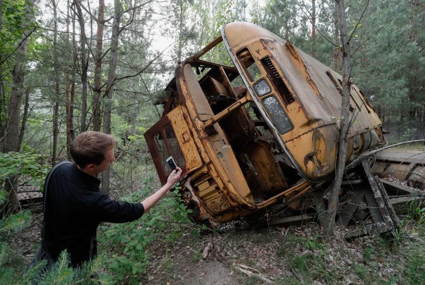 Pengunjung berfoto dekat bus yang ditinggalkan begitu saja setelah insiden nuklir Chernobyl di Rusia.