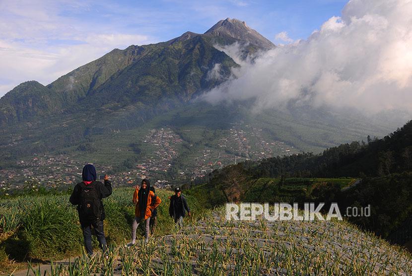 Pengunjung berfoto dengan latar belakang Gunung Merapi di Selo, Boyolali, Jawa Tengah, Selasa (3/7).