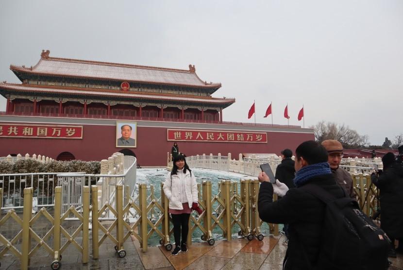 Pengunjung berpose di depan gerbang utama objek wisata Kota Terlarang, Beijing, beberapa saat setelah hujan salju, Kamis (14/2/2019) petang.