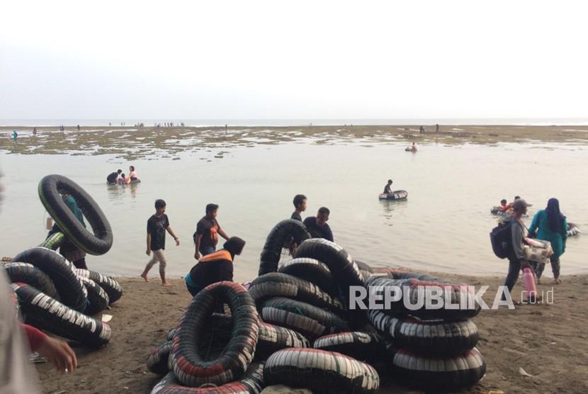 Pengunjung di Pantai Sindangkerta yang terletak di Desa Sindangkerta, Kecamatan Cipatujah, Kabupaten Tasikmalaya,