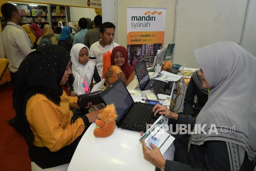 Pengunjung Islamic Book Fair (IBF) 2017 tengah mengisi aplikasi pembukaan rekening di booth Bank Syariah Mandiri (BSM) di IBF JCC Senayan, Jakarta, Kamis (4/5).