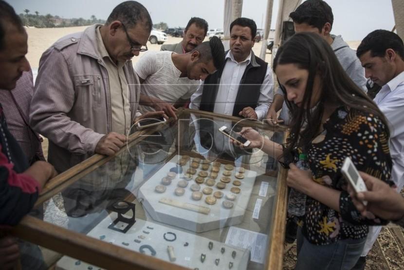 Pengunjung melihat benda peninggalan yang ditemukan di Makam Khuwy, Mesir.