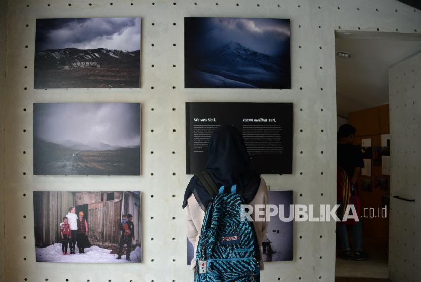 Pengunjung mengamati pameran foto Everything In Between:The Exhibition di Kopi Kalyan, Jakarta, Selasa (12/3). Pameran ini menyajikan perjalanan bersepeda Diego Yanuar bersama Marlies Fennema dari Belanda ke Indonesia, pameran foto ini akan berlangsung 12-24 Maret 2019.