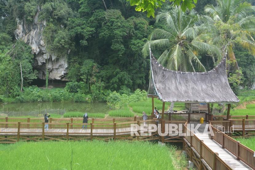 Pengunjung menikmati fasilitas jalan di atas sawah kawasan Rest Area Geopark Silokek, Kabupaten Sijunjung, Sumatera Barat, Ahad (5/9/2021). Pemerintah daerah bersama Kelompok Sadar Wisata mengembangkan wisata Rest Area sebagai pendukung kawasan Geopark Silokek Ranah Minang.