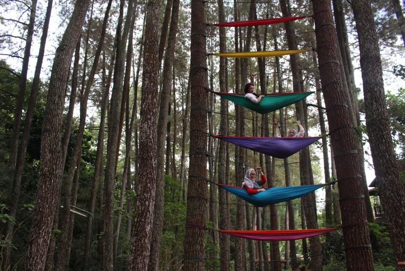 Pengunjung menikmati wahana wisata tempat tidur gantung di kawasan Taman Hutan Raya Dago, Bandung, Jawa Barat. (ilustrasi)