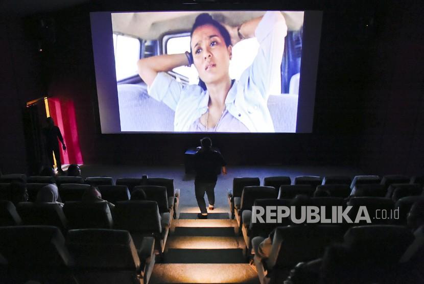 Pengunjung menonton film di bioskop rakyat di Pasar Teluk Gong, Penjaringan, Jakarta, Rabu (3/7/2019).