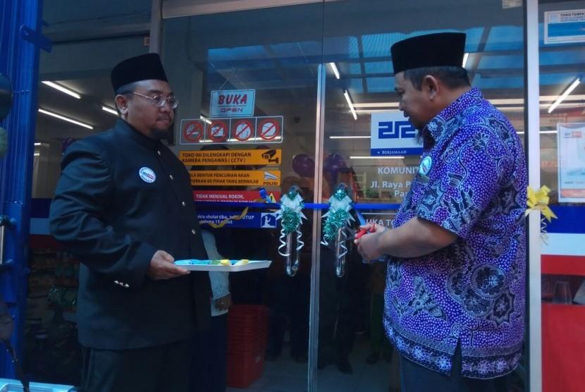 Pengurus Koperasi Syariah 212 Agus Siswanto menggunting pita sebagai tanda dibukanya gerai ke-8 212 Mart di Depok, didampingi Ketua Komunitas KS 212 Depok II, Muhammad Hidayatulloh (kiri), di Parung Bingung, Depok, Ahad (23/7).