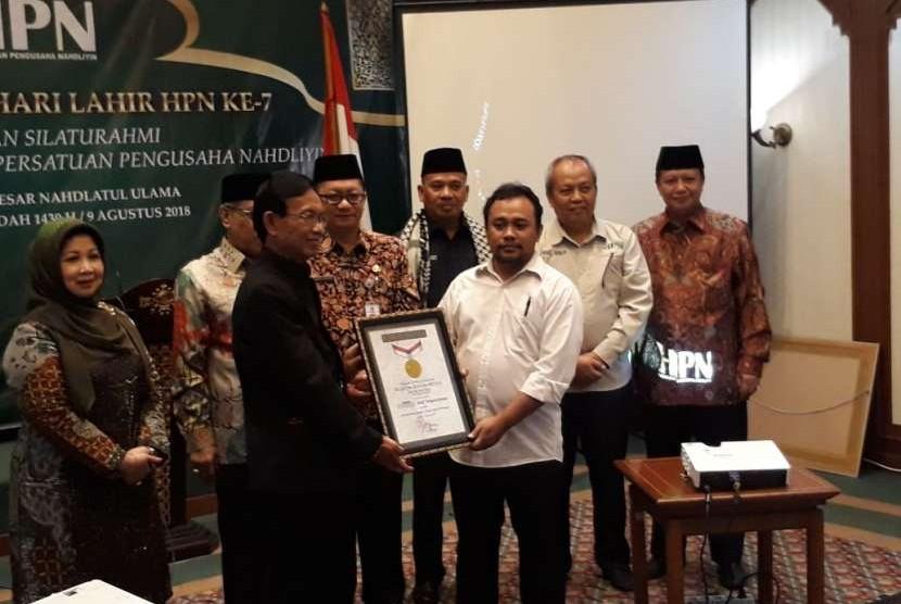 Pengusaha anggota Himpunan Pengusaha Nahdliyin (HPN), Arief Setyawiyoga (kemeja putih) saar menerima sertifikat rekor dari Musium Rekor Indonesia (MURI) dalam acara Halal bi Halal dan Hari Lahir Himpunan Pengusaha Nahdliyin (HPN) ke-7 di Gedung PBNU, Jakarta Pusat, Kamis (9/8).