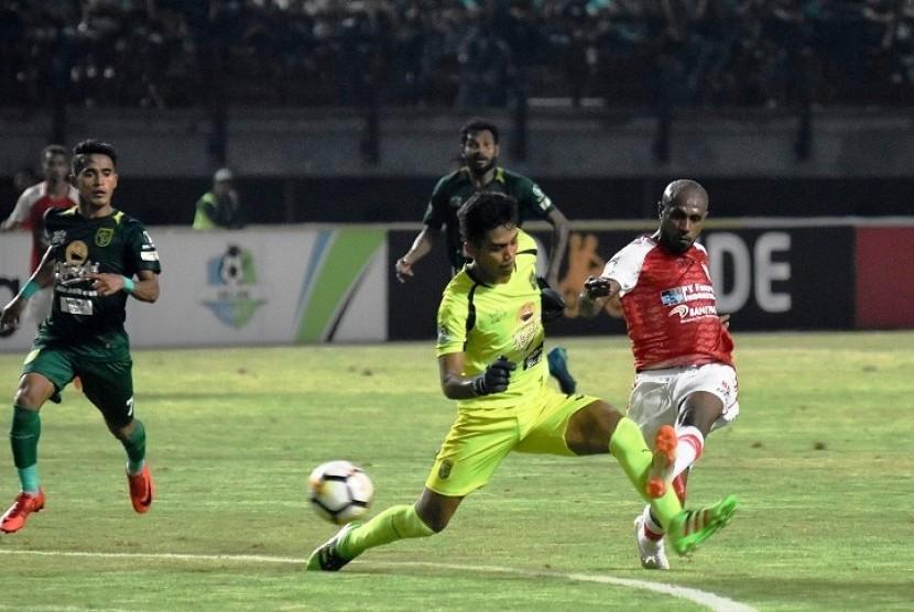 Penjaga gawang Persebaya Surabaya Miswar Saputra (tengah) berusaha menghalau bola dari penyerang Persipura Jayapura Boaz Solossa (kanan) dalam lanjutan Liga 1 di Stadion Gelora Bung Tomo, Surabaya, Jawa Timur, Selasa (29/5).