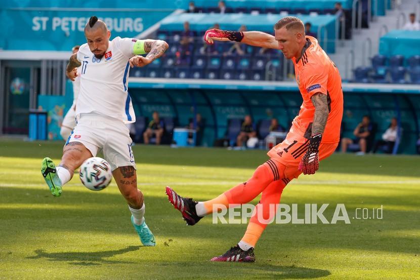 Penjaga gawang Swedia Robin Olsen menendang bola ketika pemain Slovakia Marek Hamsik mencoba menghentikannya, selama pertandingan grup E kejuaraan sepak bola Euro 2020 antara Swedia dan Slovakia, di stadion Saint Petersburg, di Saint Petersburg, Rusia,  Jumat (18/6).
