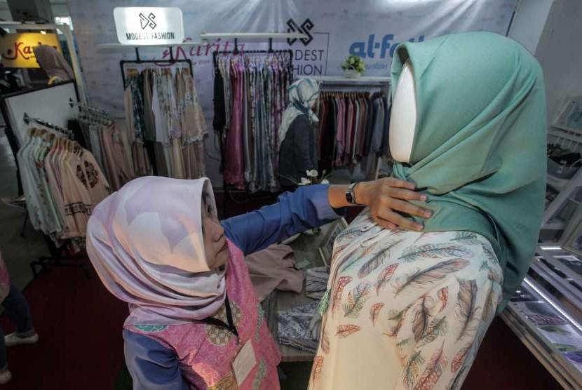Penjaga stan menata produk fesyen halal yang dipamerkan pada Jogja Halal Fest (JHF) di Jogja Expo Centre, DI Yogyakarta, Kamis (11/10).